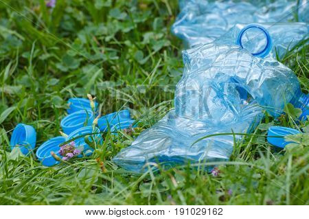 Plastic Bottles And Bottle Caps On Green Grass In Park, Concept Of Littering Of Environment