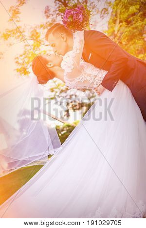 Side view of wedding couple kissing at lawn