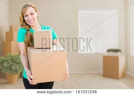 Happy Young Adult Woman Holding Moving Boxes In Empty Room In A New House.