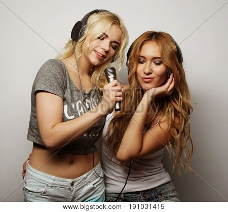 life style, happiness, emotional and people concept: beauty hipster girls with a microphone singing and having fun