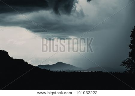 Silhouette Mountain Dark Cloudy With Rain Storm Raining Across The Sky Landscape.