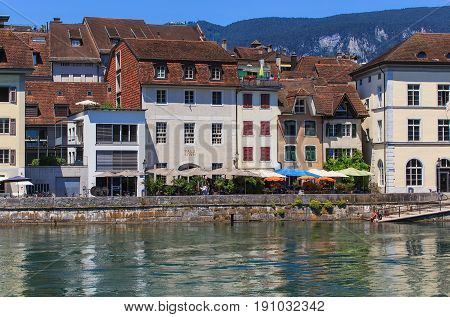 Solothurn, Switzerland - 10 July, 2016: buildings along the Aare river, people on the embankment of the river. The city of Solothurn is the capital of the Swiss canton of Solothurn and is also the only municipality of the district of the same name.