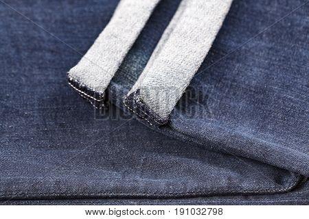 Denim blue jeans folded hemmed close up on with background