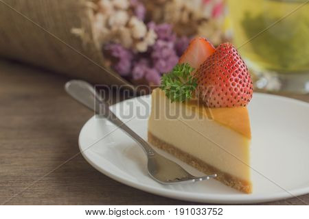 Homemade New York cheese cake on white plate decorated by strawberry and parsley. Moist and smooth classic style baked cheese cake. Copy space background of delicious strawberry New York cheese cake. Triangle slice strawberry cheese cake.