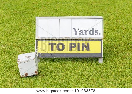 Close-up white wooden tee off area or tee box with length information sign in background.
