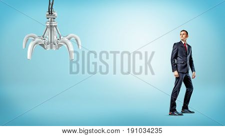 A businessman standing on blue background half-turned to look at a metallic robotic hand. Business and technologies. Robots at workplace. Competition for job.