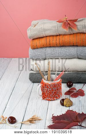 Knitted wool sweaters. Pile of knitted winter, autumn clothes on wooden background, sweaters, knitwear, cup, pen, leaf space for text