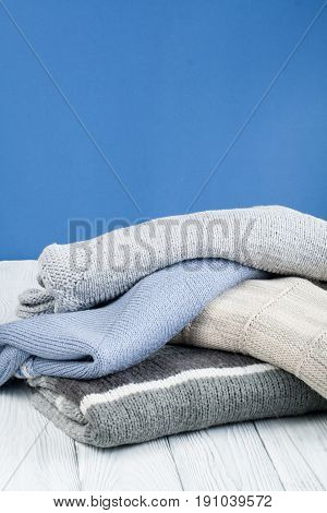 Knitted wool sweaters. Pile of knitted winter, autumn clothes on blue, wooden background, sweaters, knitwear, space for text.