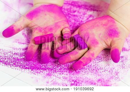 Baby's hands with pink pastel chalks. Children's Creativity. Drawing Activities for Kids