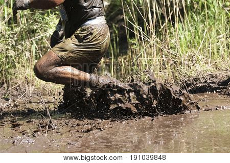 Muddy obstacle race runner in action. Mud run.