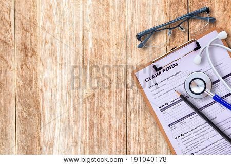 Workplace of a doctor. Stethoscopeclaim formglassespencil on wooden desk background. Top view with copy space. Healty concept.
