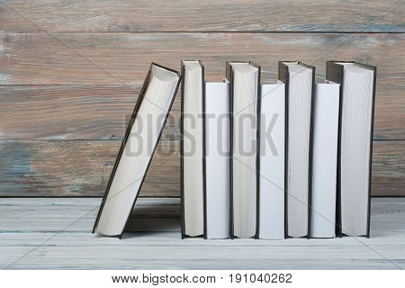 Open black and White books on wooden table, black board background. Back to school. Education business concept