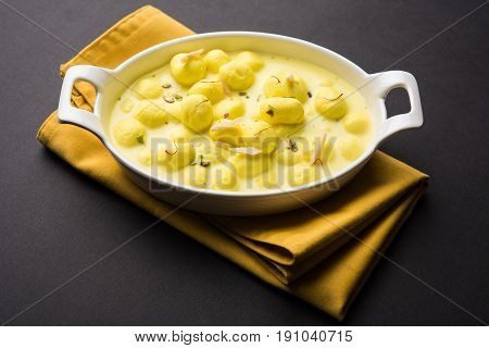 Angoori rasmalai or anguri ras malai is an Indian dessert. Made from cottage cheese which is then soaked in chashni, a sugary syrup, and rolled in fine sugar to form grape-sized balls. selective focus poster