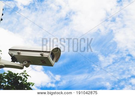 Closed circuit camera with blue sky in park