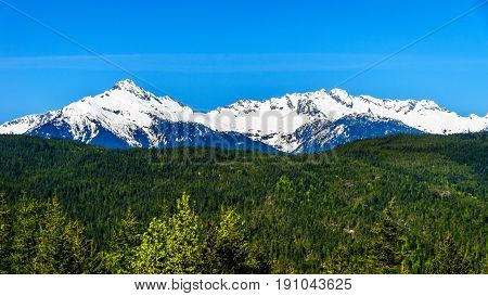 The Tantalus Mountain Range from a viewpoint along the Sea to Sky Highway between Squamish and Whistler with the snow covered peaks of Alpha Mountain, Serratus and Tantalus Mountain poster
