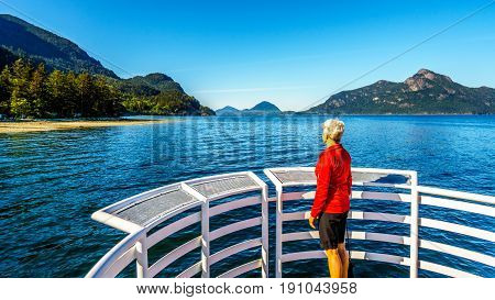 Senior woman enjoying the view of Howe Sound and surrounding mountains, with Anvil Island, along Highway 99 between Vancouver and Squamish, British Columbia. Viewed from the Porteau Cove ferry docks