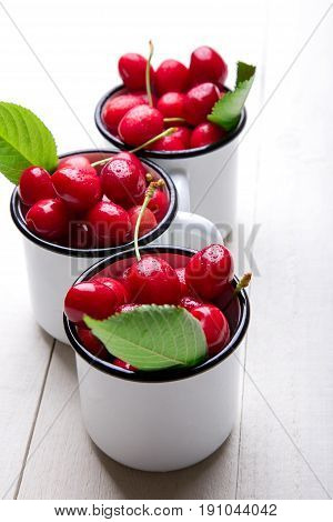 Cherry In Enamel Cup On White Wooden Background. Healthy, Summer Fruit. Cherries...