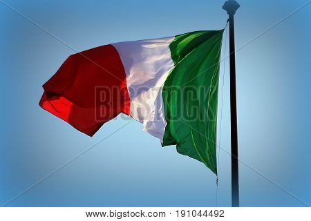 Italian flag fluttering in the wind, with blue sky .