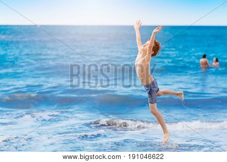 Happy Child Jumping And Playing On The Beach
