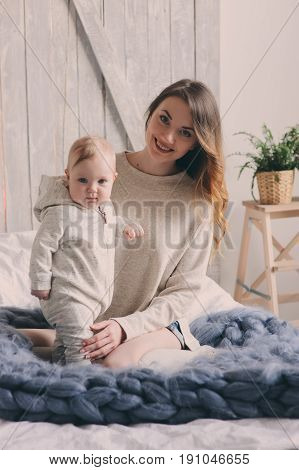 happy mother and 8 month old baby playing and relaxing at home in bedroom in the morning. Cozy family lifestyle in modern scandinavian interior.