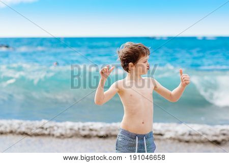 Confident Little Boy Showing His Muscles While Playing At The Beach