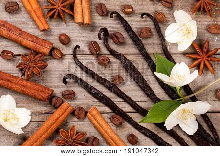 Vanilla sticks and cinnamon with anise and coffee beans on a old wooden background.
