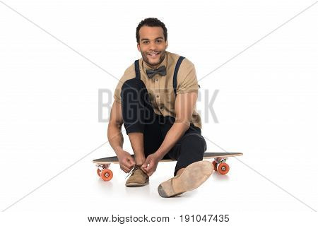 Smiling Young Man Sitting On Skateboard And Tying Shoelaces