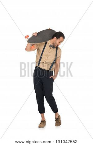 Surprised young stylish man holding skateboard on shoulder and looking down