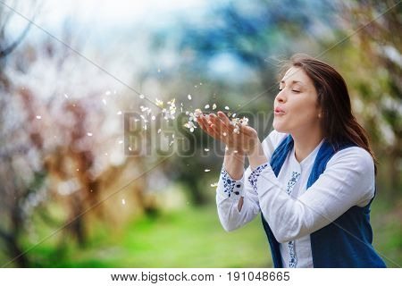 A woman makes a wish blowing off the petals of flowers from her palms. She is full of hope standing in the midst of a blooming apricot garden