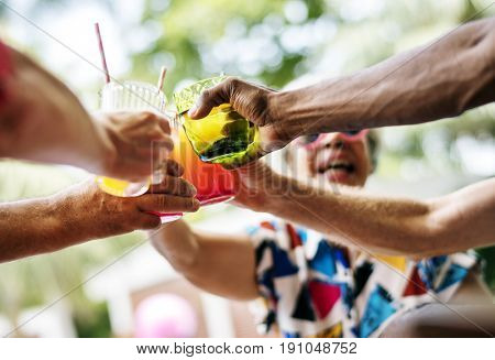 Group of diverse senior adult enjoying beverage by the pool together