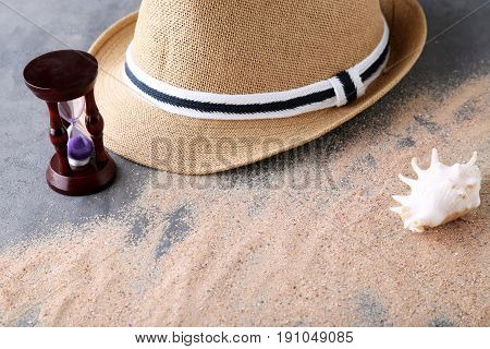 Hourglass With Beach Hat And Seashell On Grey Wooden Table