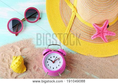 Pink Alarm Clock With Beach Hat And Sunglasses On Blue Wooden Table