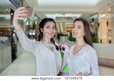 Two beautiful girls makes selfie in a shopping centre with a bag of gifts. Smiling posing for the camera. To make purchases