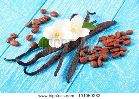 Vanilla sticks and coffee beans with flower and leaf on a blue wooden background.