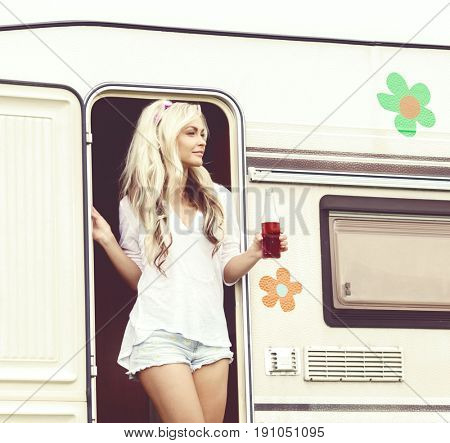 Young, attractive hippy girl standing in trailerâ??s door with bottle of refreshing drink. Holiday, journey, vacation concept.