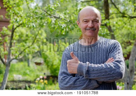 Mature man sitting in garden near apple tree in countryside. He shows thump up.