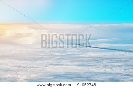 Plane flying above the clouds in the early morning. The horizontal frame.