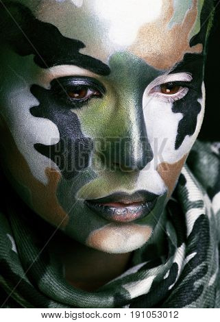 Beautiful young fashion woman with military style clothing and face paint make-up, khaki colors