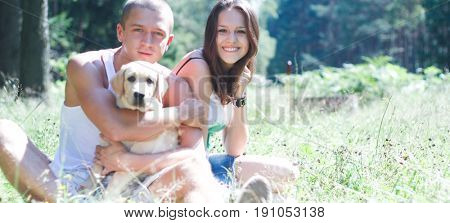 A smiling couple with their dog outdoors