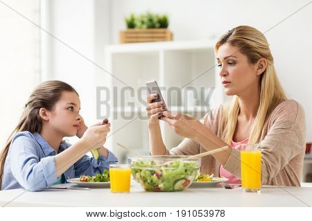 family, communication and people concept - sad girl looking at her mother with smartphone having dinner at home