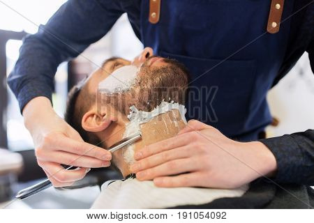 grooming and people concept - man and barber hands with straight razor shaving beard at barbershop
