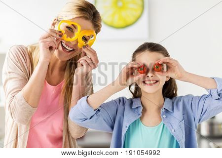 healthy eating, family and people concept - happy mother and daughter cooking vegetables and having fun at home kitchen