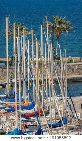 Top of sailing ship masts in marina near sea
