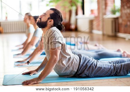 fitness, yoga and healthy lifestyle concept - group of people doing cobra pose on mats at studio