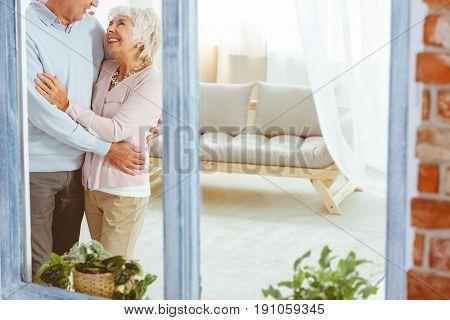 Happy smiling elderly man and woman hugging in elegant stylish apartment
