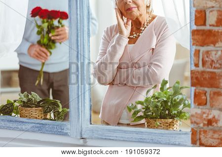 Man surprising sad senior woman staring at window with flowers