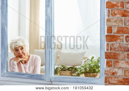 Senior elegant woman lost in thought by the window in stylish apartment