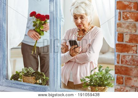 Elegant man with flowers surprising unhappy offended woman looking at her telephone