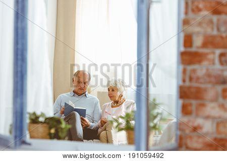 Elderly sitting man reading book to elegant woman drinking tea