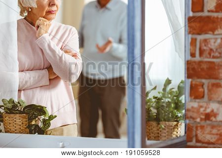 Senior man and woman arguing in apartment